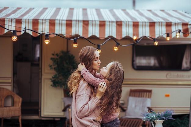 Sluit omhoog portret van moeder en weinig dochter die en pret in platteland op camper van vakantie kussen hebben
