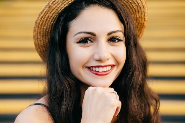 Sluit omhoog portret van mooi donkerbruin wijfje met aardige samenstelling en dunne rode lippen die zacht glimlachen