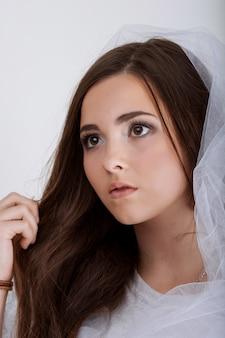 Sluit omhoog portret van mooi jong vrouwengezicht. geïsoleerd op een witte muur. portret van een vrouwelijk model.