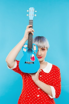 Sluit omhoog portret van mooi popachtig meisje met kort licht violet haar die de ukelele van de rode kledingsholding over blauwe muur dragen