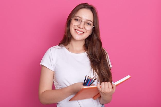 Sluit omhoog portret van mooi studentenmeisje klaar om nota's in voorbeeldenboek te maken, hebbend kijkend