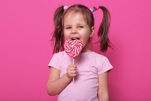 Sluit omhoog portret van mooi vrouwelijk kind die grote roze spiraalvormige lolly houden