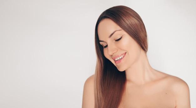 Sluit omhoog portret van mooie half naakte natuurlijke schoonheidsvrouw met perfecte huid en haar isoleerde witte muur. reiniging van gezondheidszorg. huidverzorging spa concept.