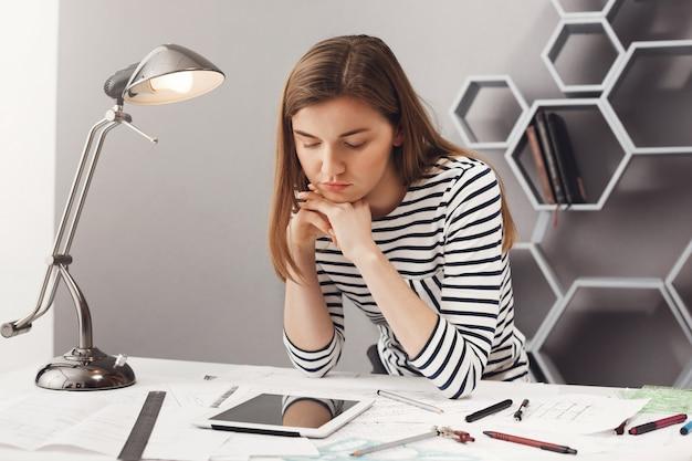 Sluit omhoog portret van mooie jonge ernstige vrouwelijke architectenstudent met bruin haar in gestreepte blik, houdend hoofd met handen, kijkend in digitale tablet met vermoeide gezichtsuitdrukking, op zoek naar voorbeeld