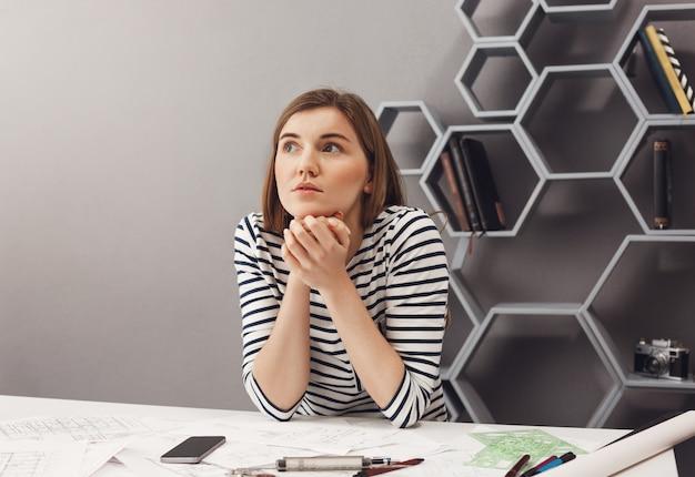 Sluit omhoog portret van mooie jonge europese donkerharige vrouwelijke ontwerperzitting bij lijst in het samenwerken ruimte, kijkend opzij met dromerige uitdrukking, ongerust makend over de vergadering van morgen.