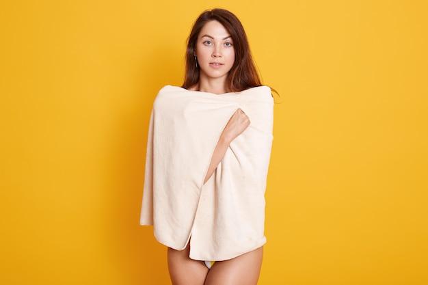 Sluit omhoog portret van mooie jonge vrouw met donker staright haar die verpakte verse witte badhanddoek stellen
