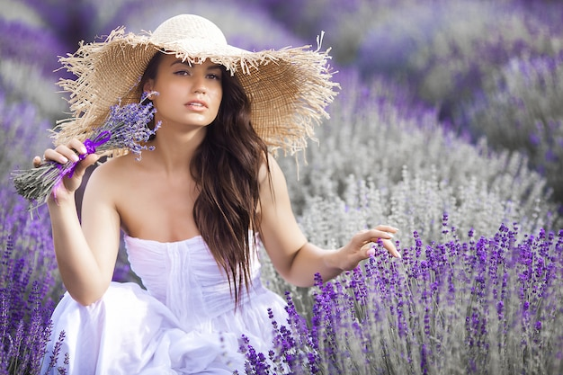 Sluit omhoog portret van mooie jonge vrouw op lavendelgebied.