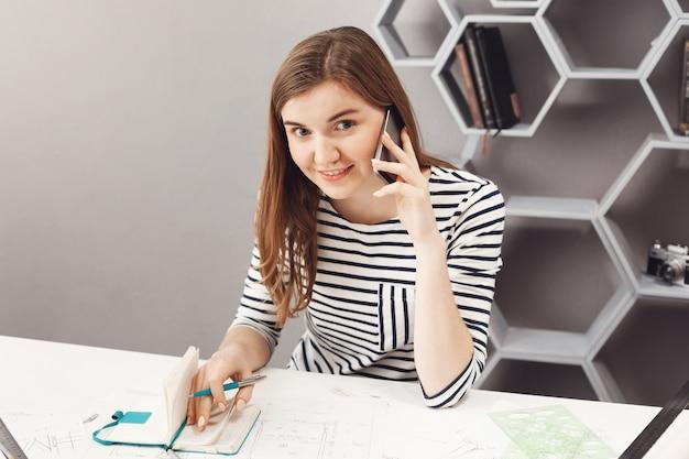 Sluit omhoog portret van mooie vrolijke jonge vrouwelijke freelance architectzitting bij lijst in bureau, sprekend op telefoon met persoon van team, schrijvend werkfouten in notitieboekje