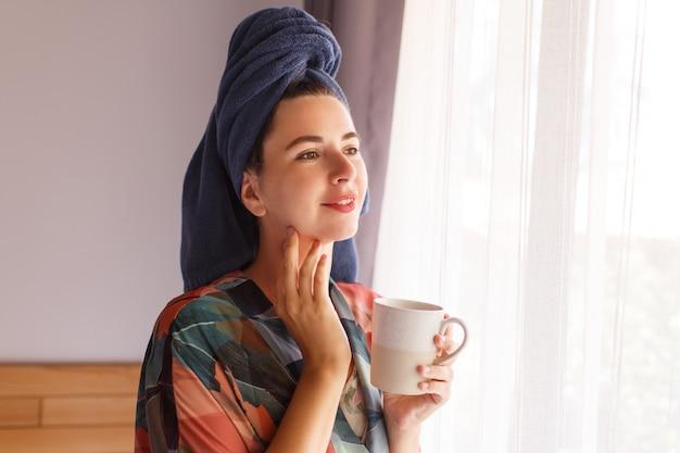 Sluit omhoog portret van mooie vrouw die in handdoek en badjasontwaken in ochtendzitting op bed wordt verpakt en koffie drinkt