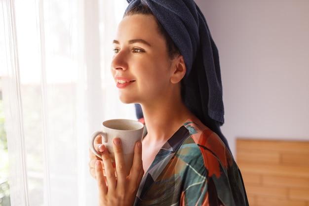 Sluit omhoog portret van mooie vrouw die in handdoek en badjasontwaken in ochtendzitting op bed wordt verpakt en thee drinkt