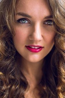Sluit omhoog portret van natuurlijk schoonheidsmodel, lichtgrijze ogen en heldere sexy lippen, gekrulde lichtbruine haren.