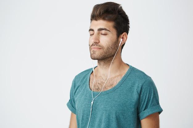 Sluit omhoog portret van ontspannen rijp kaukasisch mannetje die blauw overhemd dragen, met vreedzame gezichtsuitdrukkingen en gesloten ogen luisterend aan muziek tijdens ochtendyoga.