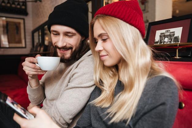 Sluit omhoog portret van paar bekijkend telefoon in koffie