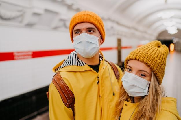Sluit omhoog portret van paar in medische beschermende maskers gekleed in gele windjacks bij metrostation wachtend op een trein. trieste gedachten over pandemisch coronavirus. covid-19 virusconcept.