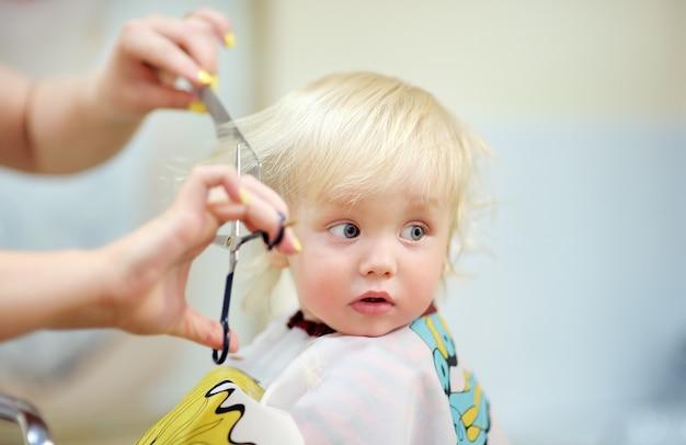 Sluit omhoog portret van peuterkind die zijn eerste kapsel krijgen
