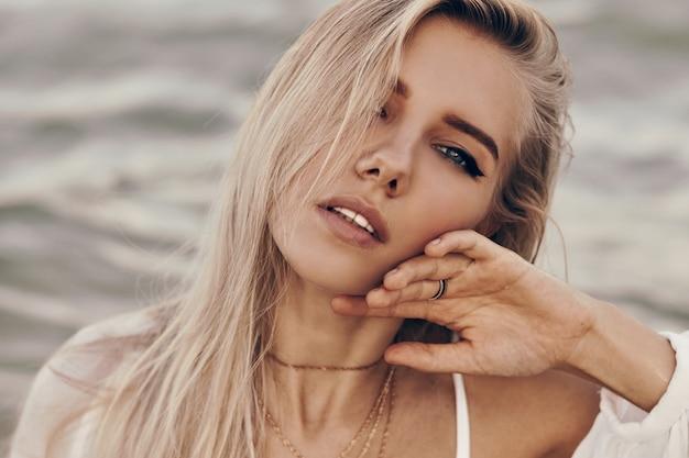 Sluit omhoog portret van schitterende blonde vrouw met perfecte huid en blauwe ogen die op het strand stellen