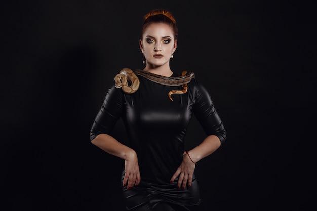 Sluit omhoog portret van sexy vrouw met slang in latexuitrusting