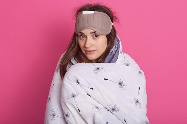 Sluit omhoog portret van slaperige vrouw met slaapmasker op hoofd en het dragen van deken