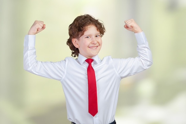 Sluit omhoog portret van sterke glimlachende jongen die spieren tonen