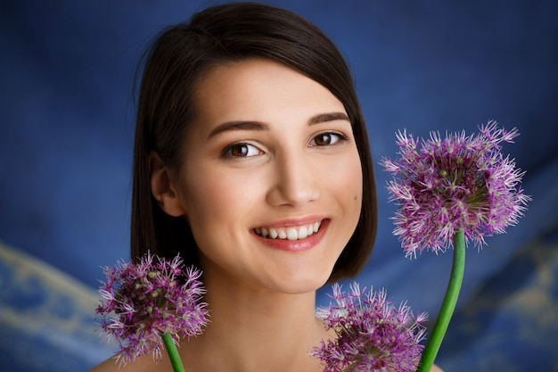 Sluit omhoog portret van tedere jonge vrouw met lila bloemen over blauwe muur