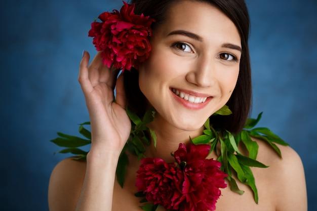 Sluit omhoog portret van tedere jonge vrouw met rode bloemen over blauwe muur