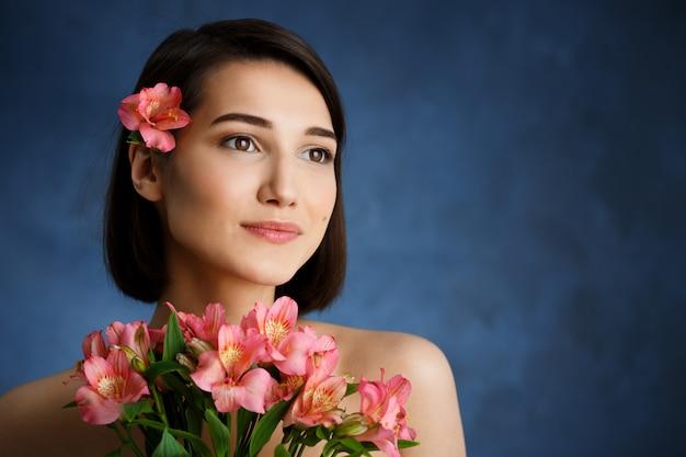 Sluit omhoog portret van tedere jonge vrouw met roze bloemen over blauwe muur