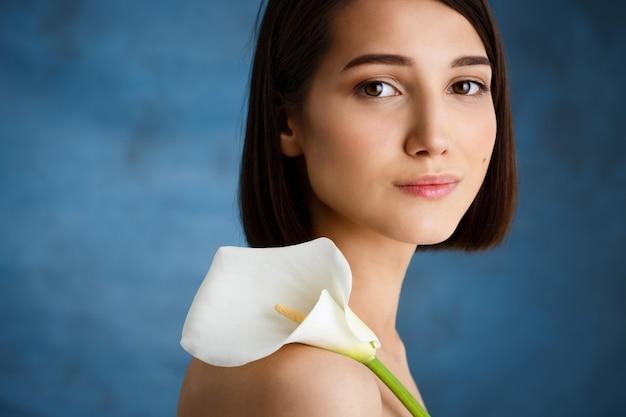 Sluit omhoog portret van tedere jonge vrouw met witte bloem over blauwe muur
