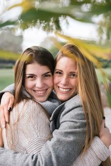 Sluit omhoog portret van twee glimlachende jonge vrouwen