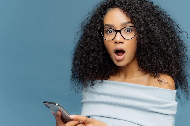 Sluit omhoog portret van verbijsterde jonge vrouw met afro-kapsel, houdt mond wijd open