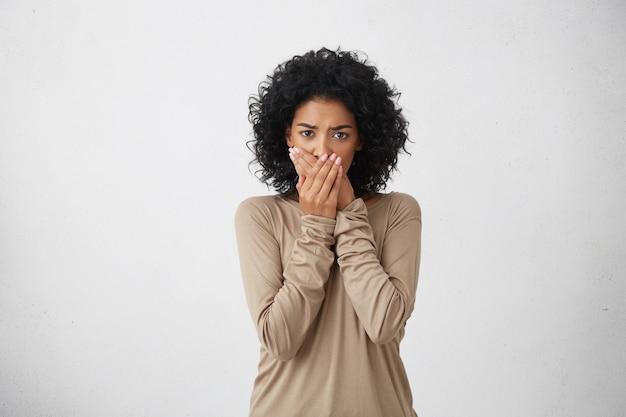 Sluit omhoog portret van verstoorde bang zwarte vrouw, die haar mond met beide handpalmen bedekt om schreeuwend geluid te voorkomen, na het zien of horen van iets slechts. negatieve emoties, gezichtsuitdrukkingen en gevoelens