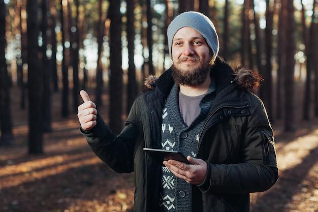 Sluit omhoog portret van volwassen mannelijke wandelaar gebruikend digitale tablet