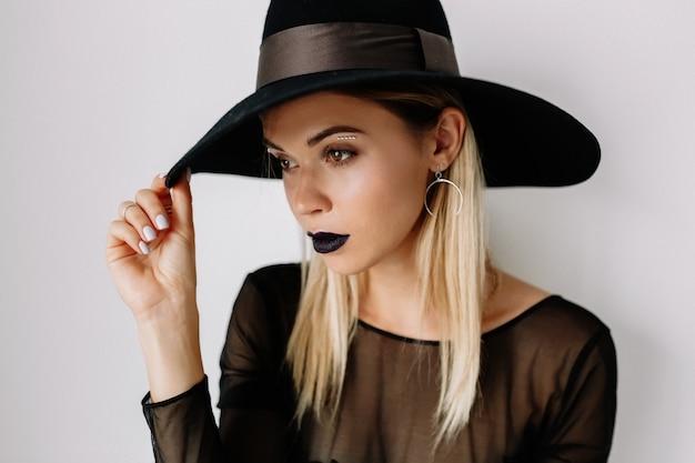 Sluit omhoog portret van vrij beminnelijke vrouw met blond haar die hoed dragen die over geïsoleerde muur stellen