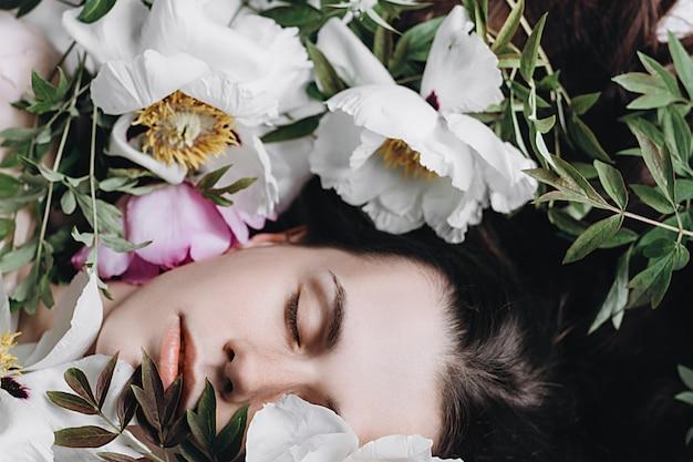 Sluit omhoog portret van vrij donkerbruine vrouw in witte en purpere bloemen. kaukasische meisjesontspanning in het park met buiten pioenen