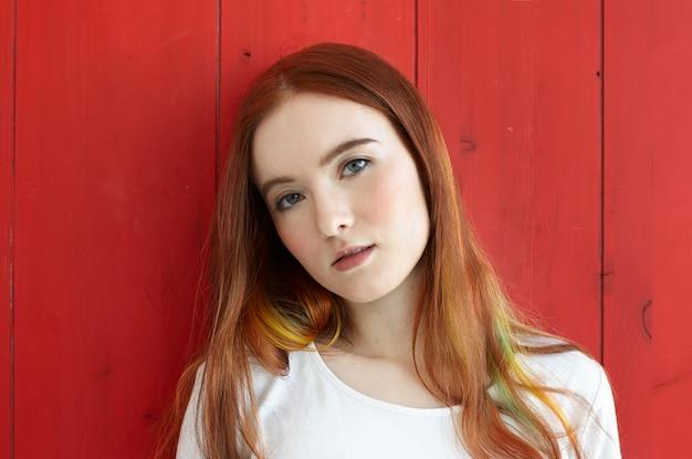 Sluit omhoog portret van vrij gemengd ras tienermeisje dat nadenkend en dromerig kijkt. gorgeus roodharige student vrouw met gekleurde lokken van haar en groene ogen