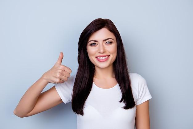 Sluit omhoog portret van vrij jonge gelukkige glimlachende vrouw die duim op grijze ruimte toont