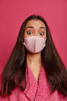 Sluit omhoog portret van vrij jonge vrouw die een beschermend geïsoleerd gezichtsmasker draagt