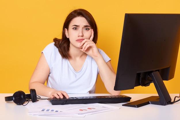 Sluit omhoog portret van vrij jonge vrouwelijke student gebruikend bureaucomputer in een universiteitsbibliotheek