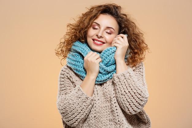 Sluit omhoog portret van vrolijk dromerig glimlachend mooi donkerbruin krullend meisje in gebreide sweater en grijze halswarmer over beige muur