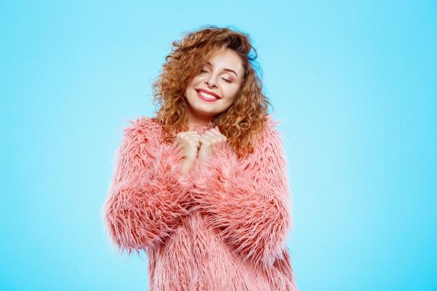 Sluit omhoog portret van vrolijk glimlachend dromerig mooi donkerbruin krullend meisje in roze bontjas over blauwe muur