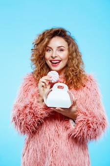 Sluit omhoog portret van vrolijk glimlachend mooi donkerbruin krullend meisje dat in roze bontjas heemst over blauwe muur eet