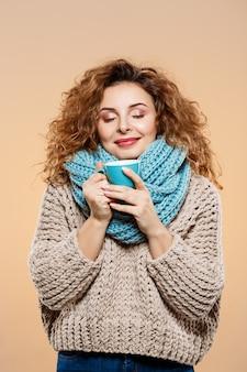 Sluit omhoog portret van vrolijk glimlachend mooi donkerbruin krullend meisje in gebreide sweater en grijze neckwarmer holdingskop over beige muur