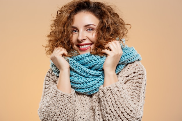 Sluit omhoog portret van vrolijk glimlachend mooi donkerbruin krullend meisje in gebreide sweater en grijze neckwarmer over beige muur