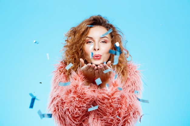 Sluit omhoog portret van vrolijk glimlachend mooi donkerbruin krullend meisje in roze bontjas met confettien op voorgrond over blauwe muur