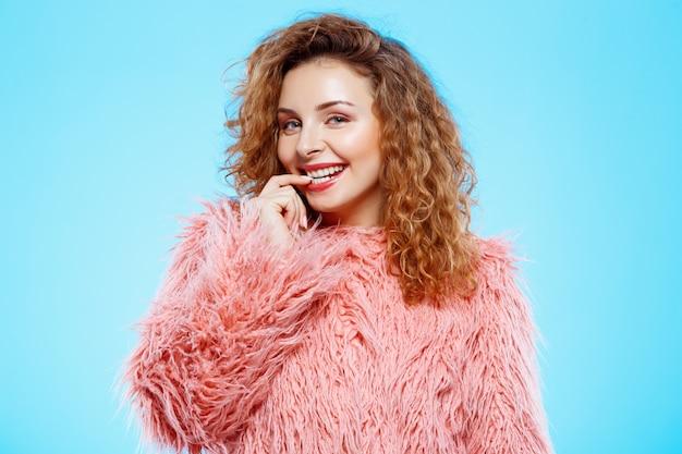 Sluit omhoog portret van vrolijk glimlachend mooi donkerbruin krullend meisje in roze bontjas over blauwe muur