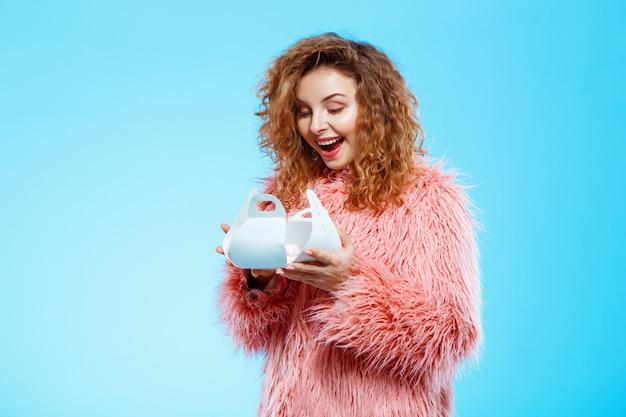 Sluit omhoog portret van vrolijk glimlachend verrast mooi donkerbruin krullend meisje in roze bontjas over blauwe muur