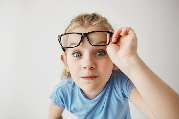 Sluit omhoog portret van vrolijk klein meisje met grappig blonde haar en blauwe ogen imiteert volwassen persoon met glazen met verraste uitdrukking.