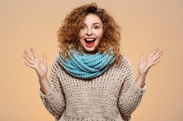 Sluit omhoog portret van vrolijk verrast glimlachend mooi donkerbruin krullend meisje in gebreide sweater en grijze neckwarmer over beige muur