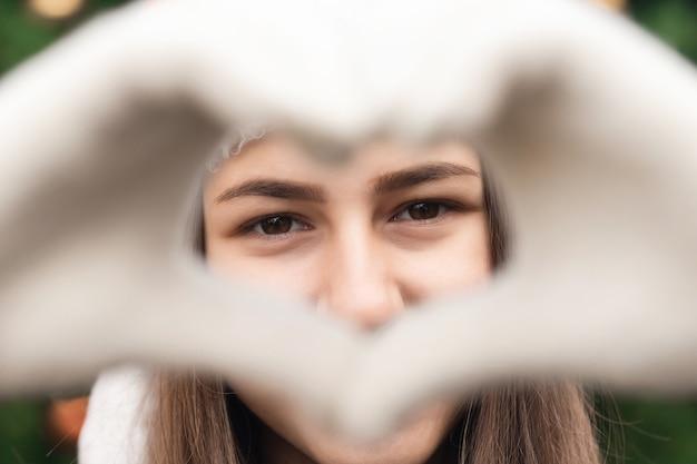 Sluit omhoog portret van vrouw die een hoed van de kerstman met emotie draagt en hart van vingers maakt. tegen de achtergrond van een kerstboom