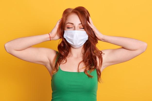 Sluit omhoog portret van vrouw die medisch masker en groen t-shirt dragen, haar hoofd aanraken, geïsoleerd stellen, met hoofdpijn