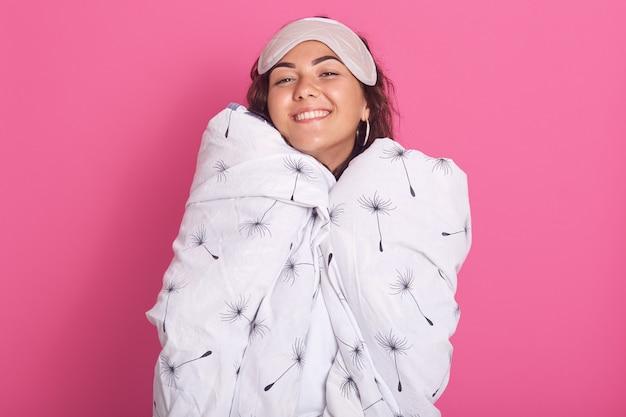 Sluit omhoog portret van vrouw met slaapmasker op haar voorhoofd, verpakte witte deken met paardebloem